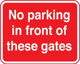 No parking in front of these gates red background sign.